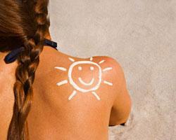 Naturystka z narysowanym za pomocą kremu słoneczkiem na plecach